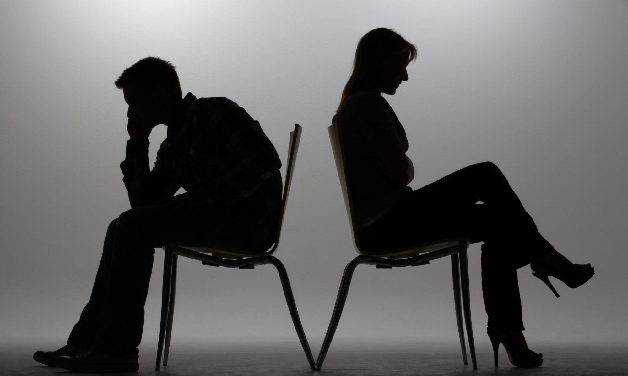 Shilouette von Mann und Frau, Rücken an Rücken sitzend