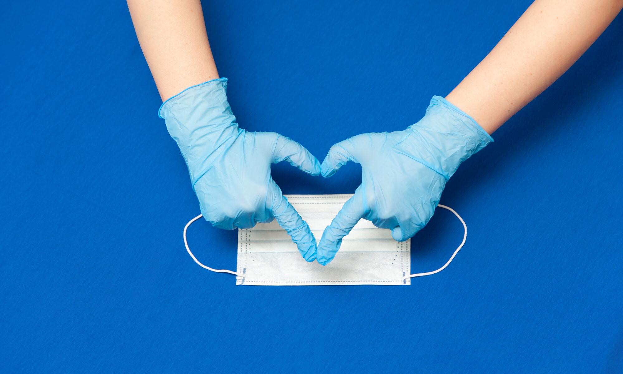 Hände mit Schutzhandschuhen und Mundschutz formen ein Herz