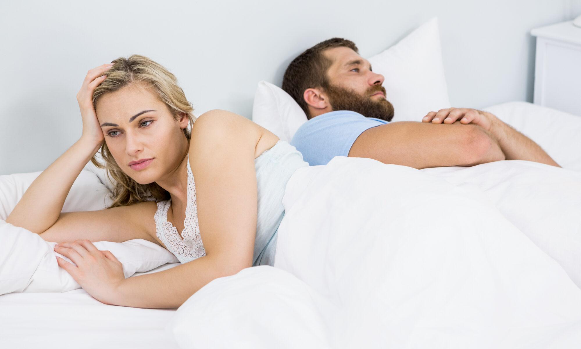 Paar liegt gelangweilt im Bett