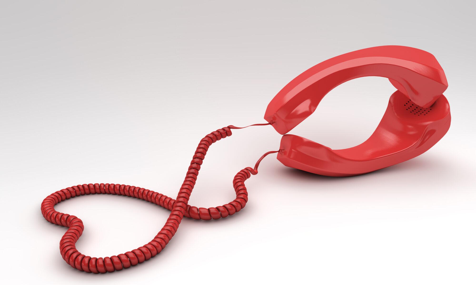 Rote Telefonhörer liegen aufeinander und deuten Sex an