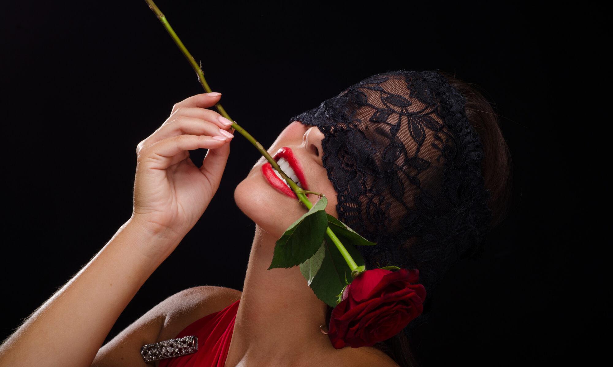 Frau mit Augenmaske aus schwarzer Spitze und Rose im Mund
