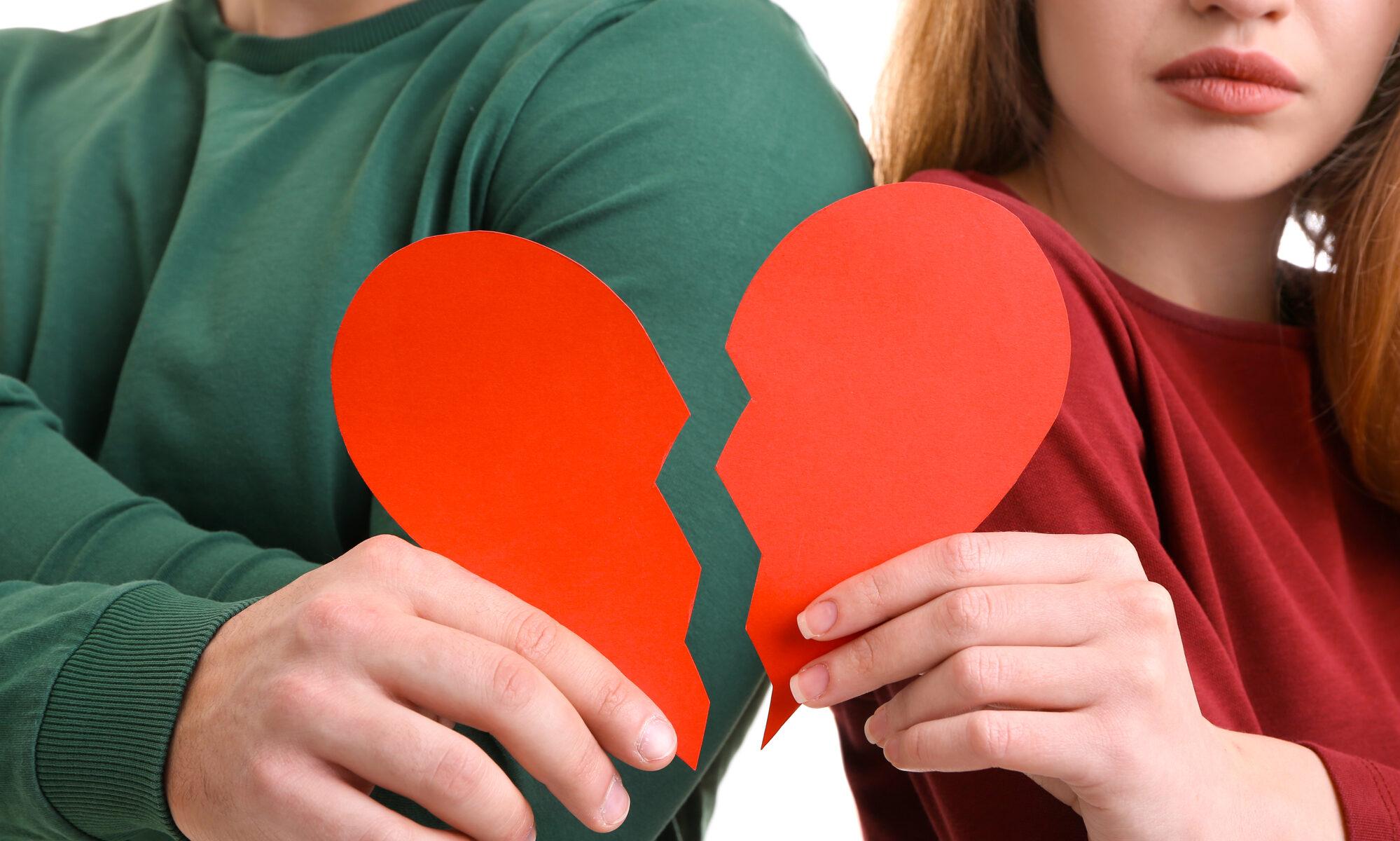 Junges Paar hält gebrochenes Herz in der Hand