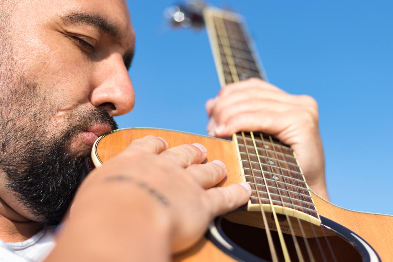 Mann küsst innig seine Gitarre