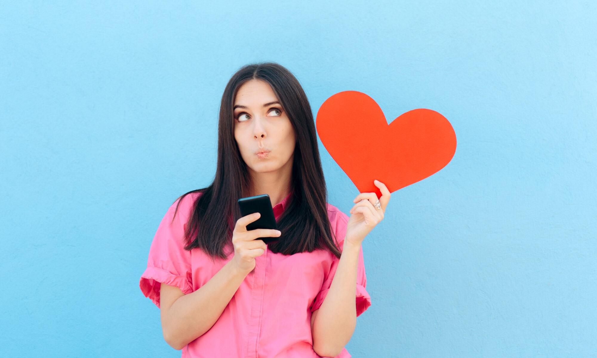 Verliebte Frau mit Herz und Handy in der Hand