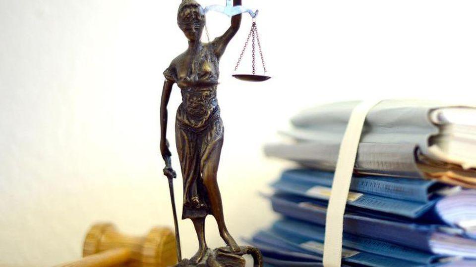 Ein Modell der Justitia steht auf einem Tisch. Foto: Volker Hartmann/dpa/Archivbild