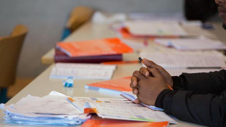 Arbeitsmaterialien auf dem Tisch einer Vorbereitungsklasse mit Flüchtlingen. Foto: Arno Burgi