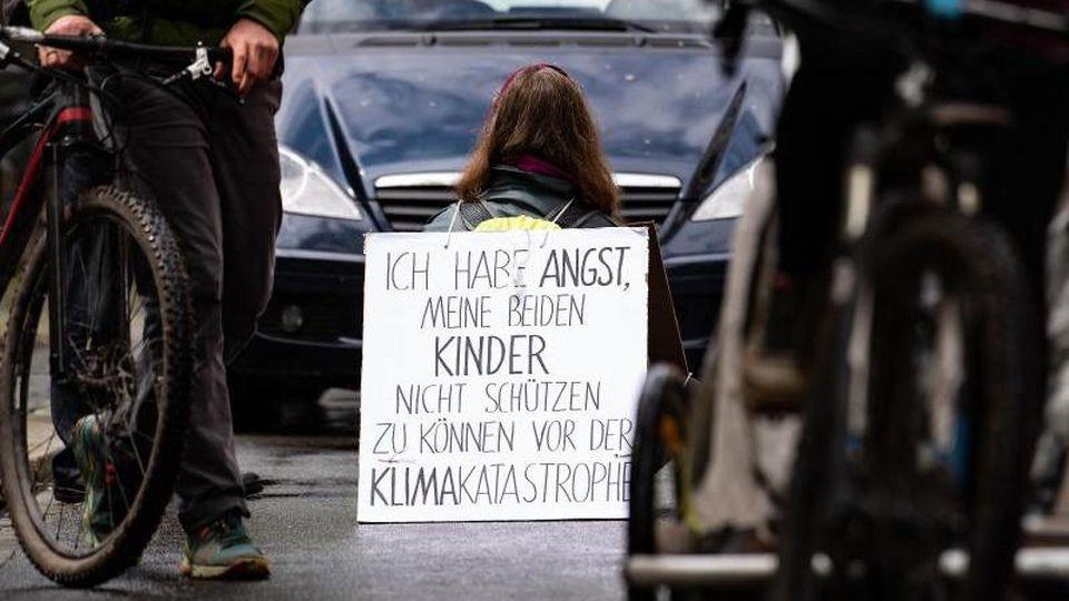 Eine Aktivistin sitzt mit einem Plakat auf der Straße. Foto: Swen Pförtner/dpa/aktuell