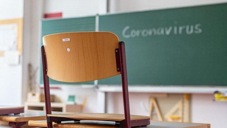 """""""Coronavirus"""" steht auf einer Tafel in einem leeren Klassenzimmer. Foto: Armin Weigel/dpa/Symbolbild"""