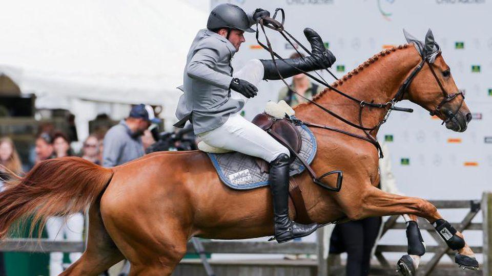 Der Reiter Philipp Weishaupt aus Deutschland fällt von seinem Pferd Che Fantastica herab. Foto: Rolf Vennenbernd