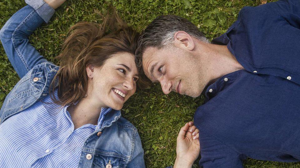 Ein verliebtes Paar liegt auf einer Wiese