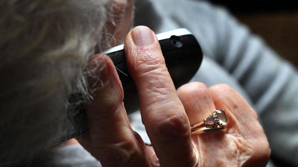 Eine ältere Frau telefoniert mit einem schnurlosen Festnetztelefon. Foto: Karl-Josef Hildenbrand/dpa/Symbolbild