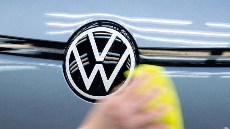 Ein Mitarbeiter von Volkswagen streicht mit einem Tuch über ein Fahrzeug von VW. Foto: Sebastian Kahnert/dpa-Zentralbild/ZB/Symbolbild
