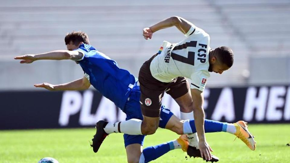 Der Karlsruher Philip Heise (l) und Paulis Daniel-Kofi Kyereh kämpfen um den Ball. Foto: Uli Deck/dpa