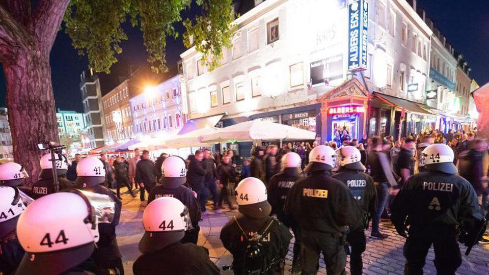 Polizeibeamte beobachten einen Fanmarsch von Anhängern des Hamburger SV. Foto: Jonas Walzberg