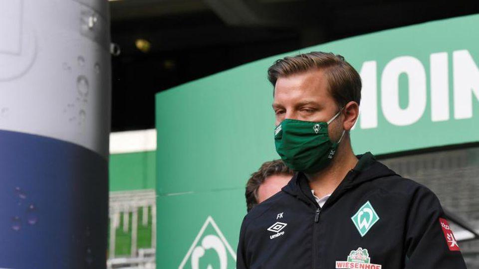 Florian Kohfeldt, Trainer von Werder Bremen, kommt mit Gesichtsmaske aufs Spielfeld vor der Partie gegen Mönchengladbach. Foto: Fabian Bimmer/reuters - Pool/dpa