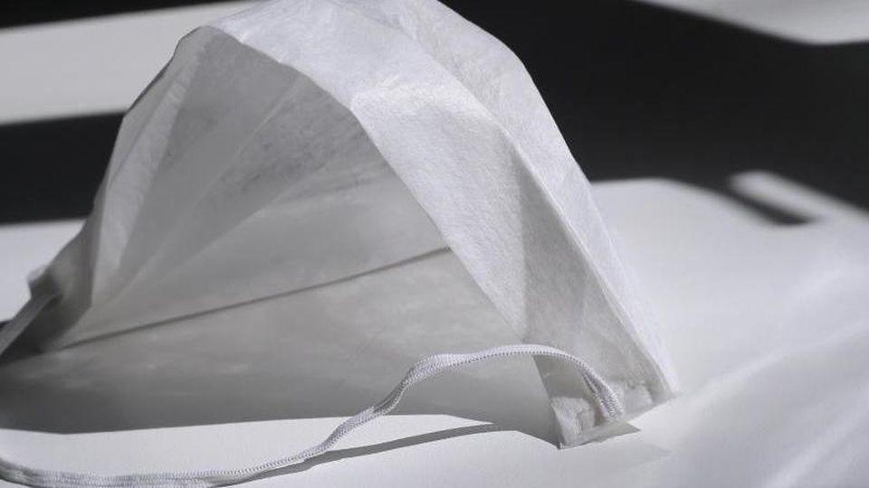 Ein medizinischer Mundschutz liegt auf einem Tisch im Sonnenschein. Foto: Karl-Josef Hildenbrand/dpa/Archivbild
