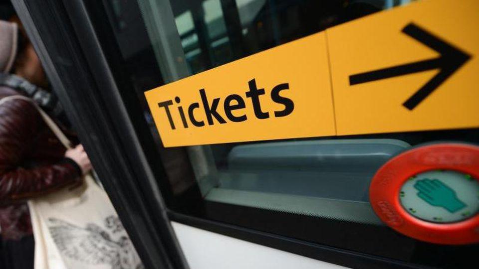 """Ein Aufkleber mit der Aufschrift """"Tickets"""" ist an einem Bus angebracht. Foto: Arne Dedert/dpa"""