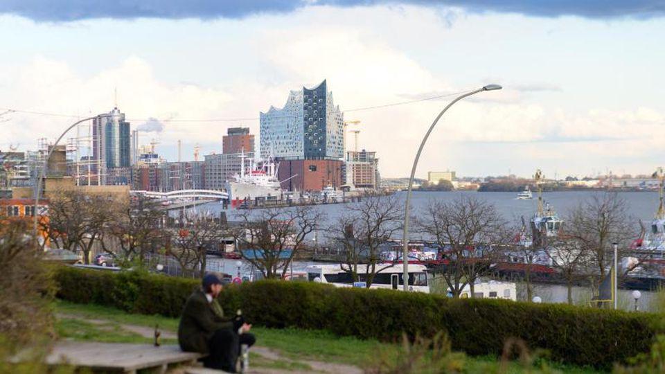 Graue Wolken ziehen über die Elbe, Elbphilharmonie und den Hafen am St. Pauli Fischmarkt. Foto: Jonas Walzberg/dpa