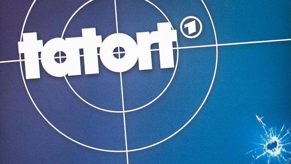 """Das Logo des ARD-Kultkrimis """"Tatort"""" und ein Absperrband sind zu sehen. Foto: Christoph Schmidt/dpa/Archivbild"""