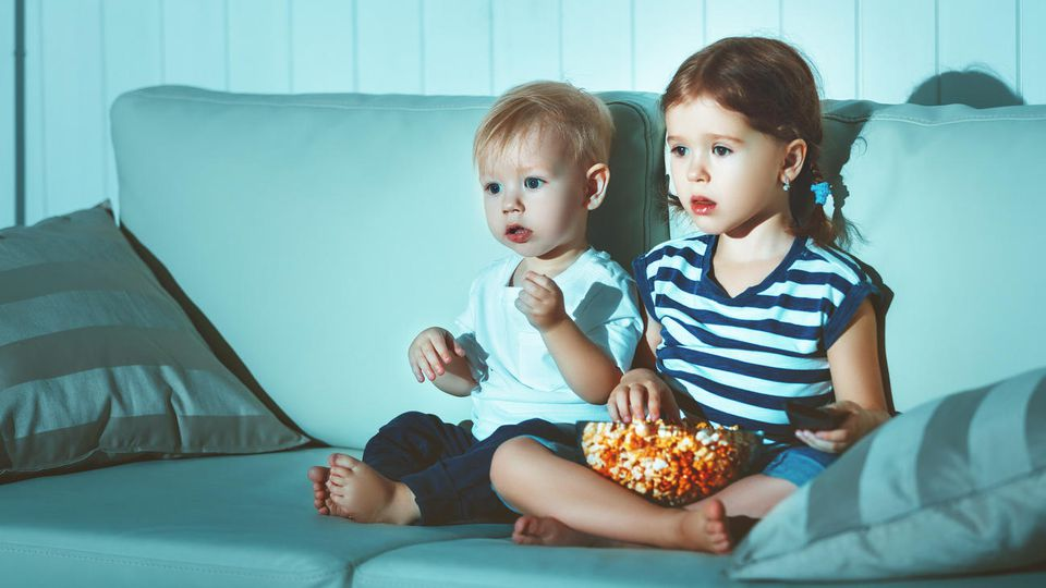 Geschwisterkinder, die abends fernsehen