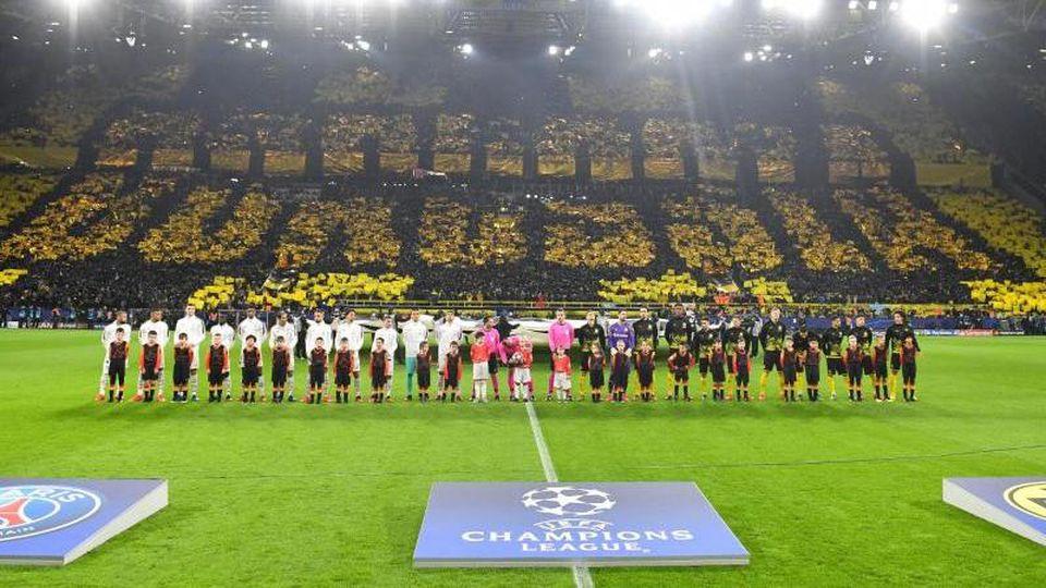 Spieler von PSG (l) und von Borussia Dortmund stehen vor dem Spiel am Feld. Foto: Bernd Thissen/dpa/Archivbild