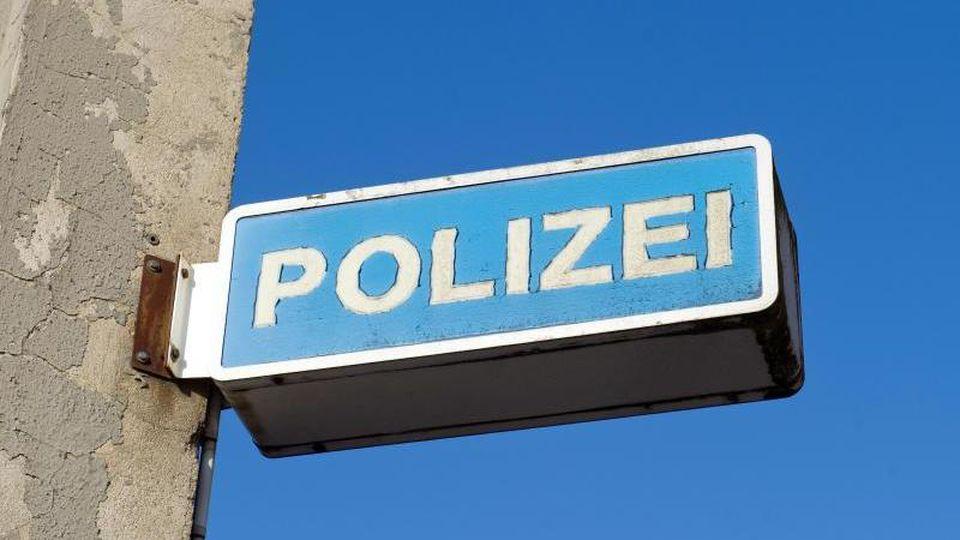 Blick auf das Hinweisschild eines Polizeireviers. Foto: Stefan Sauer/Archiv