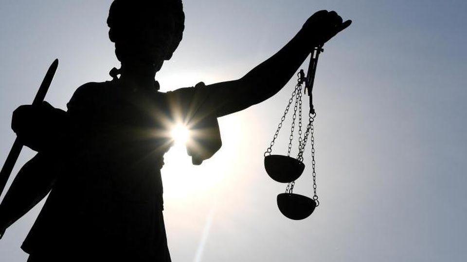 Die Statue der Justitia steht mit einer Waage und einem Schwert in der Hand. Foto: Arne Dedert/dpa/Symbolbild