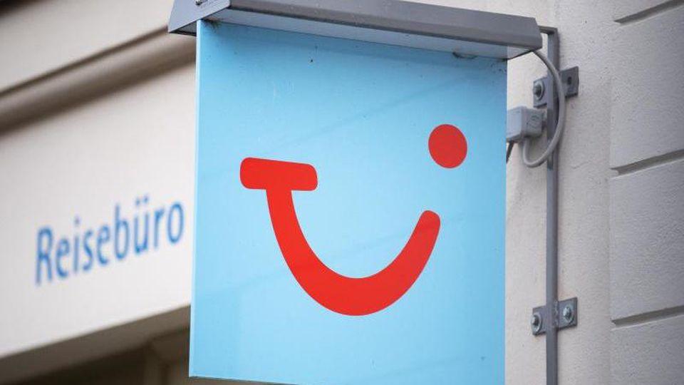 Das Logo des Reiseunternehmens TUI hängt neben einem geschlossenen Reisebüro. Foto: Soeren Stache/dpa-Zentralbild/dpa/Archivbild