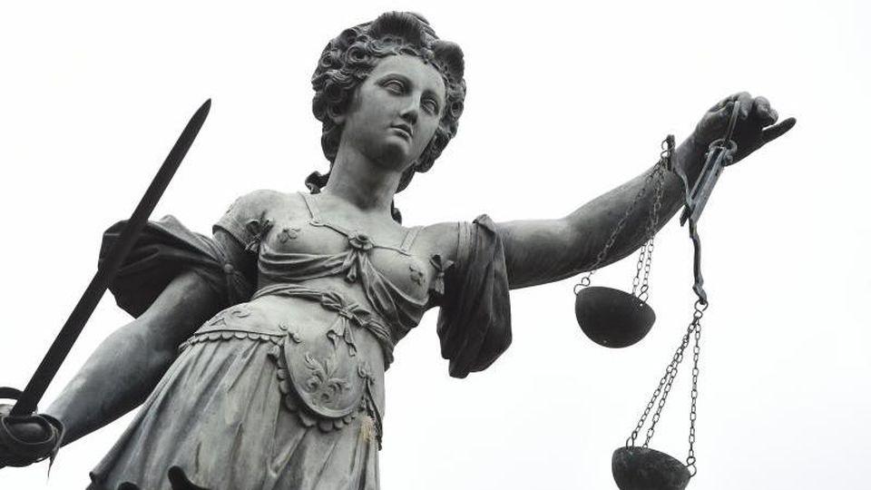Eine Bronzestatue der Justitia steht unter freiem Himmel. Foto: Arne Dedert/dpa/Archivbild