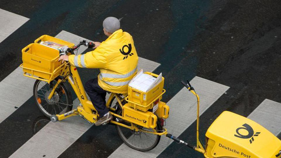 Ein Briefträger der Deutschen Post fährt mit einem Fahrrad (E-Bike) über einen Zebrastreifen. Foto: Sebastian Kahnert/dpa