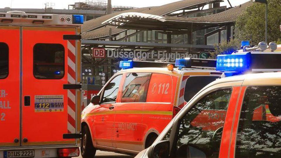 Rettungsfahrzeuge der Feuerwehr stehen mit Blaulicht vor dem Bahnhof Düsseldorf-Flughafen.Foto:David Young