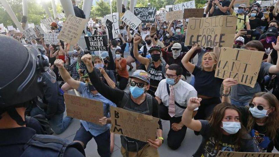 Demonstranten knien bei einem Protest vor einem Polizisten nieder. Foto: Rick Bowmer/AP/dpa