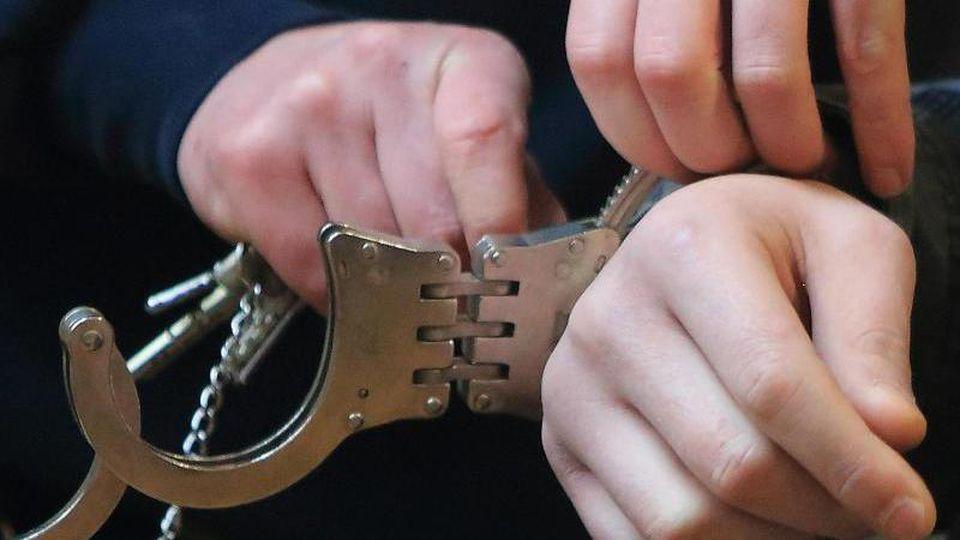 Handschellen werden einem Mann angelegt. Foto: Jens Wolf/dpa-Zentralbild/dpa/Archivbild