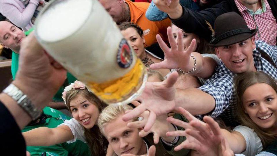 Besucher freuen sich beim Auftakt zum Oktoberfest über ihr erstes Bier. Foto: Sven Hoppe/Archivbild