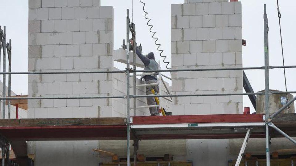 Ein Arbeiter hebt auf einer Baustelle für einen Neubau Steine auf eine Wand. Foto: Stefan Sauer/dpa