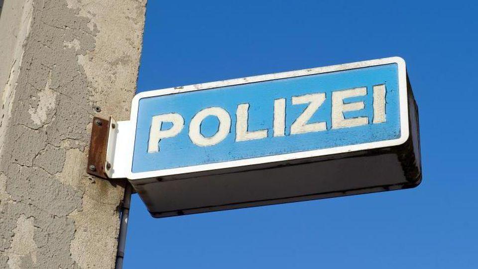 Blick auf das Hinweisschild eines Polizeireviers. Foto: Stefan Sauer/dpa-Zentralbild/dpa/Symbolbild