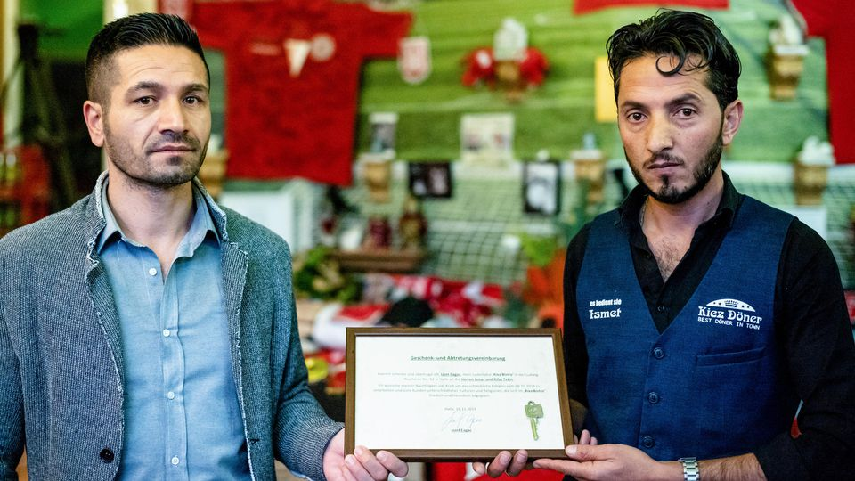 """Izzet Cagac (l), der bisherige Betreiber des Imbisses """"Kiez-Döner"""", hält bei der Wiedereröffnung die Geschenk- und Abtretungsvereinbarung an den neuen Betreiber Ismet Tekin (r)."""
