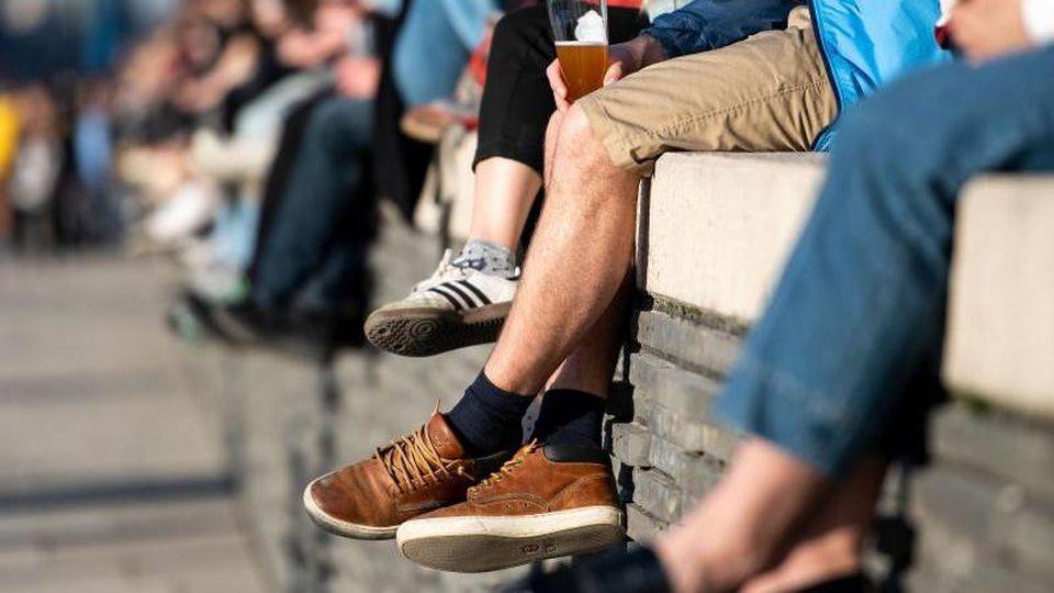 Menschen sitzen auf einer Mauer am Rheinboulevard in Köln und genießen die Sonne. Foto: Marius Becker