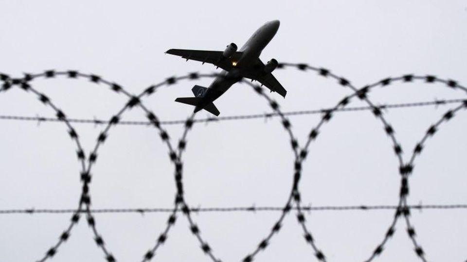 Ein Flugzeug hebt vor einem Stacheldraht in den Himmel ab. Foto: Julian Stratenschulte/dpa/Symbolbild
