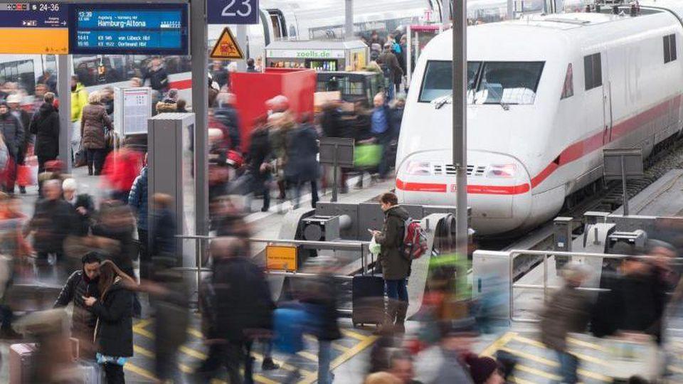 Reisende gehen am Hauptbahnhof München über eine Plattform. Foto: Tobias Hase