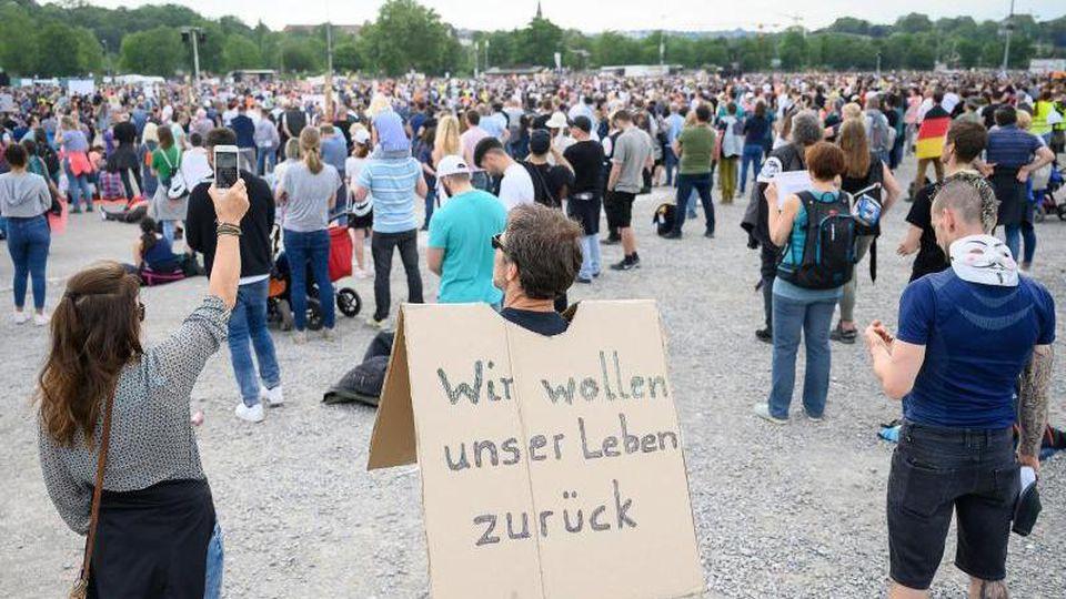 """Ein Mann steht mit einem Schild, auf dem """"Wir wollen unser Leben zurück"""" steht, innerhalb einer Demonstration. Foto: Sebastian Gollnow/dpa/Archivbild"""