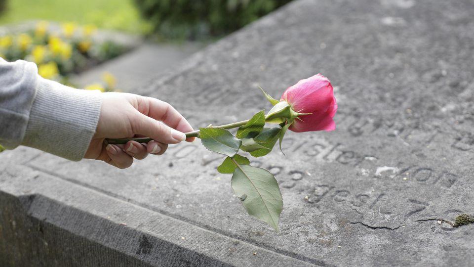 Frau mit einer Rose an einem Grabstein. (Symbolbild)