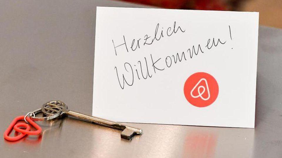Ein Schlüssel mit einem Airbnb-Anhäger und eine Herzlich-Willkommen-Karte in einer Ferienwohnung. Foto: Jens Kalaene/zb/dpa/Symbolbild