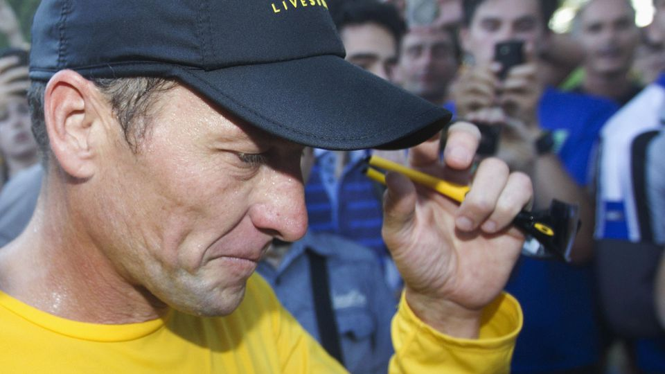File photograph of Lance Armstrong walking back to his car after running at Mount Royal park with fans in Montreal