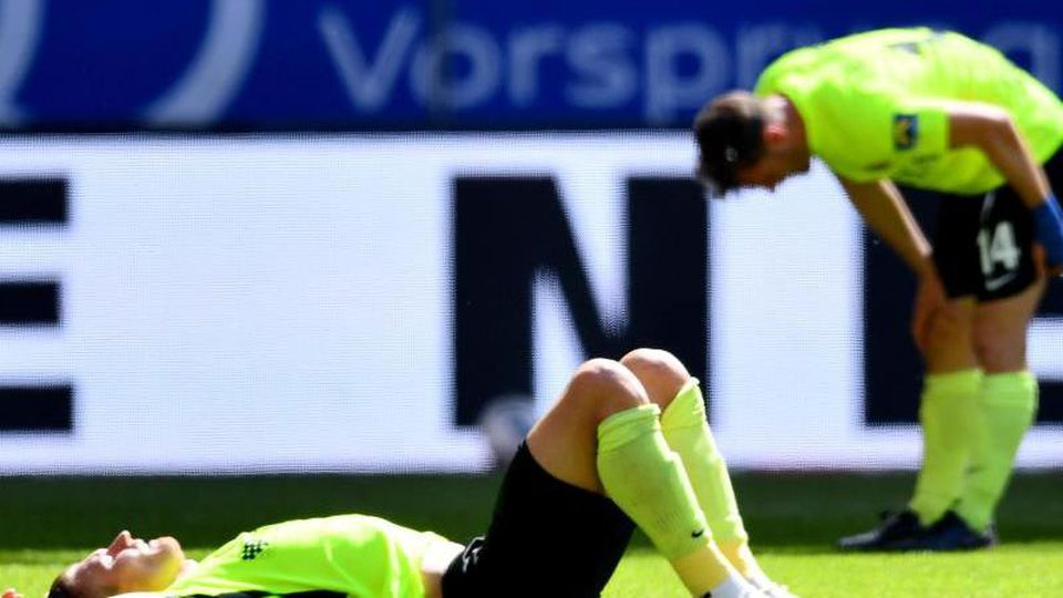 Die Wiesbadener Spieler stehen und liegen nach dem Abpfiff enttäuscht auf dem Platz. Foto: Stuart Franklin/Getty Images Europe/Pool/dpa