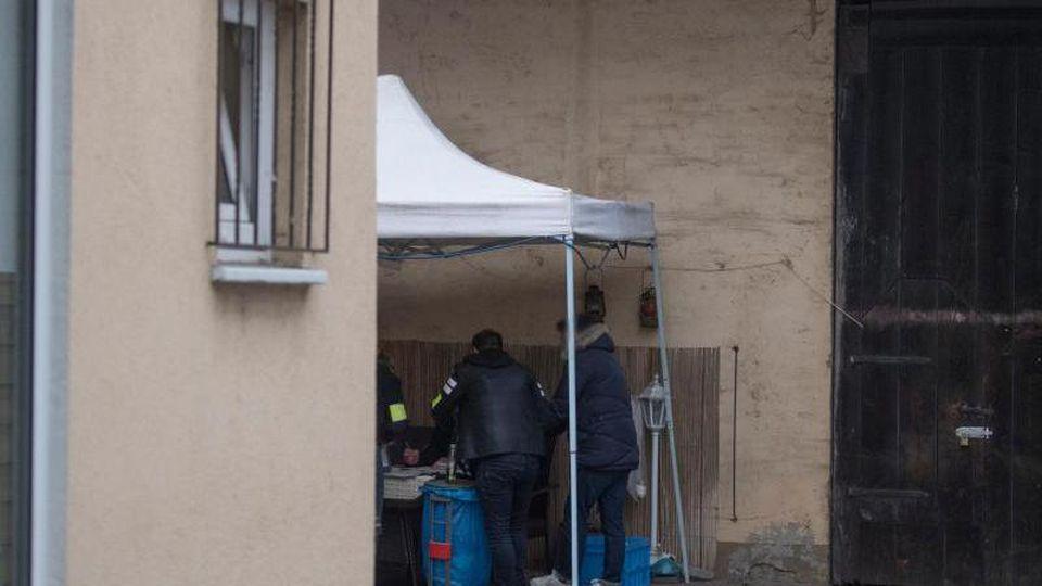 Beamte der Kriminalpolizei sichern im Hinterhof eines Hauses sichergestellte Asservate. Foto: Boris Roessler