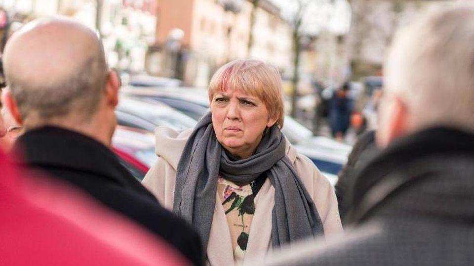 Claudia Roth (Bündnis 90/Die Grünen, M), Bundestagsvizepräsidentin, steht an einem der Anschlagsorte am Heumarkt in der Innenstadt, wo sie ein Blumengesteck niederlegte. Foto: Frank Rumpenhorst/dpa/Archivbild