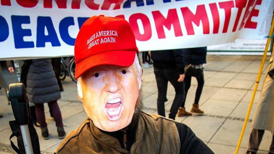 Ein Teilnehmer an der Demonstration gegen die Sicherheitskonferenz sitzt als Trump verkleidet. Foto: Sina Schuldt