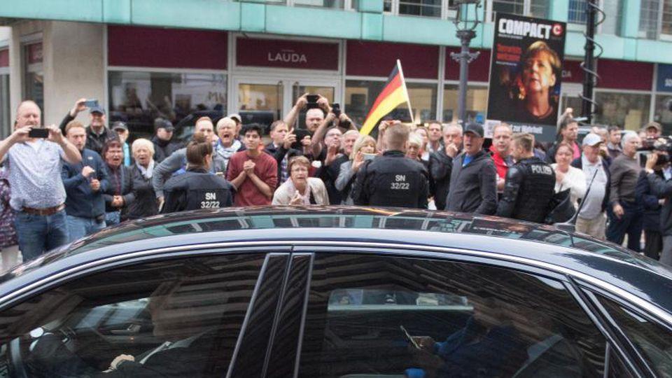 Der Dienstwagen der Bundeskanzlerin fährt an Demonstranten vor dem Albertinum vorbei. Foto: Sebastian Kahnert