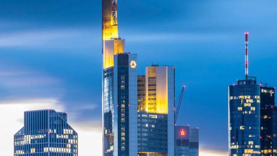 Wolken sind im Abendlicht hinter der Commerzbank und anderen Hochhäusern der Bankenskyline zu sehen. Foto: Boris Roessler/dpa/Archivbild